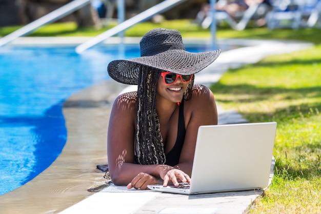 Mulher deitada na beira da piscina com um laptop. mulher afro-americana com chapéu e óculos escuros, aproveitando um dia de verão.