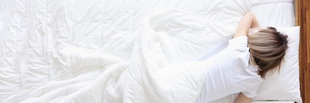 Mulher deitada na cama branca e segurando uma garrafa com álcool na mão, alcoolismo feminino e