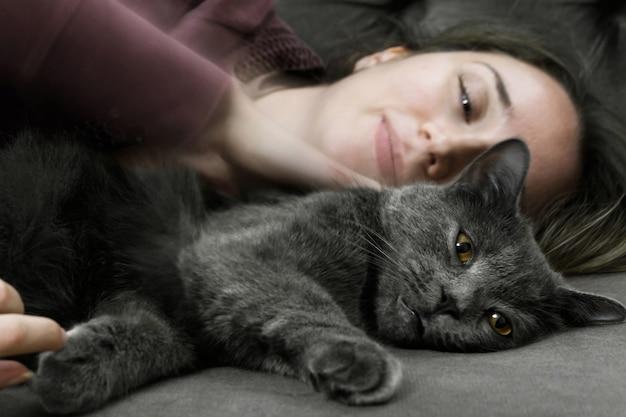 Mulher deitada na cama com gato preto britânico
