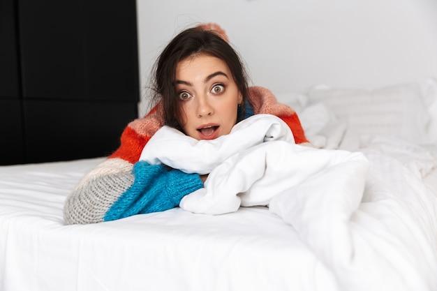 Mulher deitada na cama com os olhos abertos e expressão de surpresa