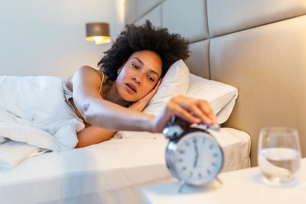 Mulher deitada na cama, desligando um despertador de manhã às 7h.