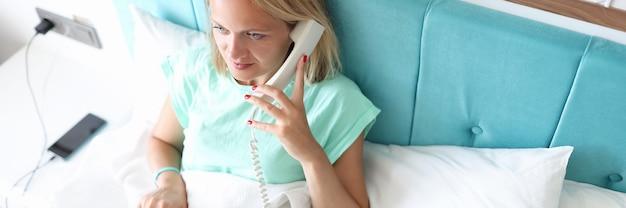 Mulher deitada na cama e disca o número do telefone
