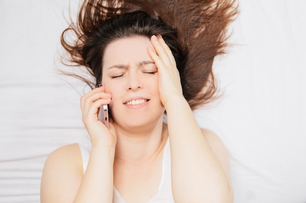 Mulher deitada na cama e falando ao telefone.