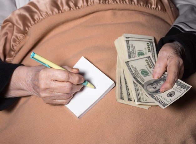 Mulher deitada na cama. segurando um dólar em dinheiro e um caderno com uma caneta em casa