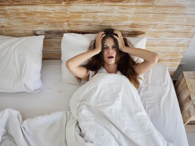 Mulher deitada na cama sob o cobertor do quarto da tristeza