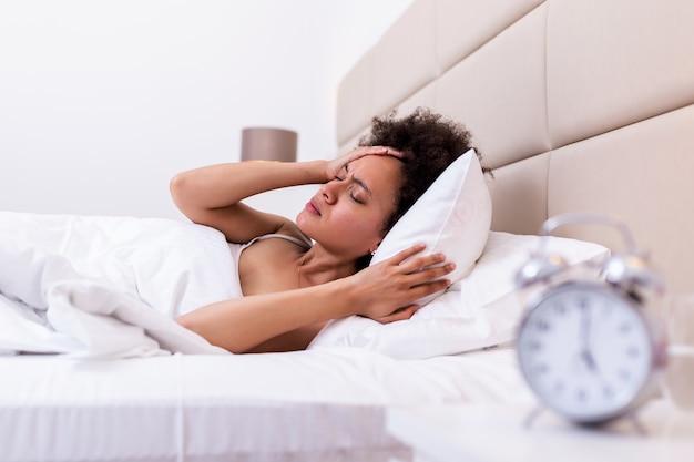 Mulher deitada na cama, sofrendo de insônia,