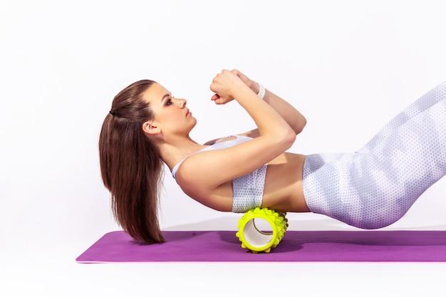 Mulher deitada na esteira de ioga usando massageador de rolo de espuma nas costas, alongando os músculos da coluna