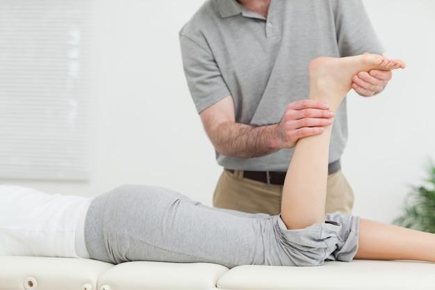 Mulher deitada na frente enquanto um fisioterapeuta examina sua perna