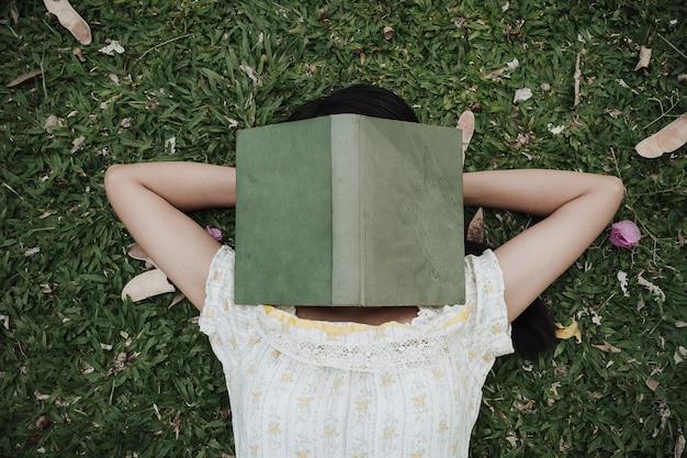 Mulher deitada na grama e dormir. jovem morena coberta o rosto com o livro.