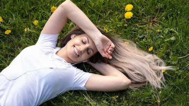 Mulher deitada na grama verde, relaxando ao ar livre, parecendo feliz e sorridente