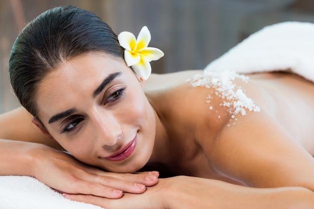Mulher deitada na mesa de massagem com esfoliação com sal nas costas