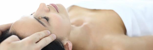 Mulher deitada na mesa de massagem com os olhos fechados, o massagista faz uma massagem facial de acupressão. serviços de rejuvenescimento em conceito de salões de beleza