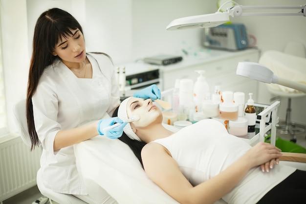 Mulher deitada na mesa de massagem em um spa enquanto uma máscara facial é aplicada em seu rosto
