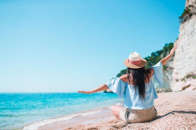 Mulher deitada na praia aproveitando as férias de verão, olhando para o mar