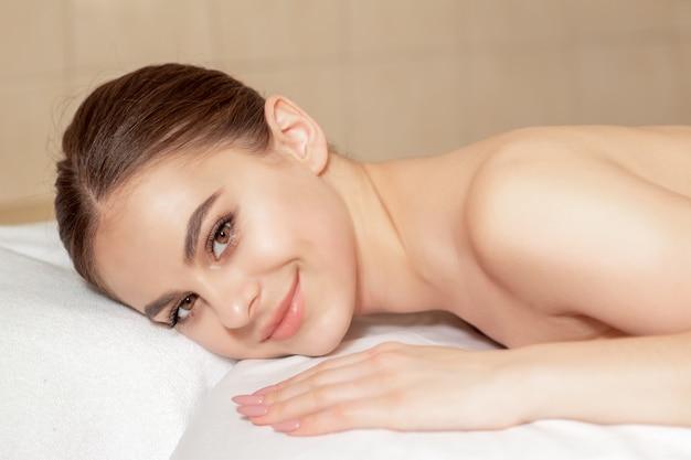 Mulher deitada na toalha no spa.