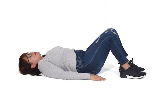 Mulher deitada no chão com as pernas apoiadas em fundo branco