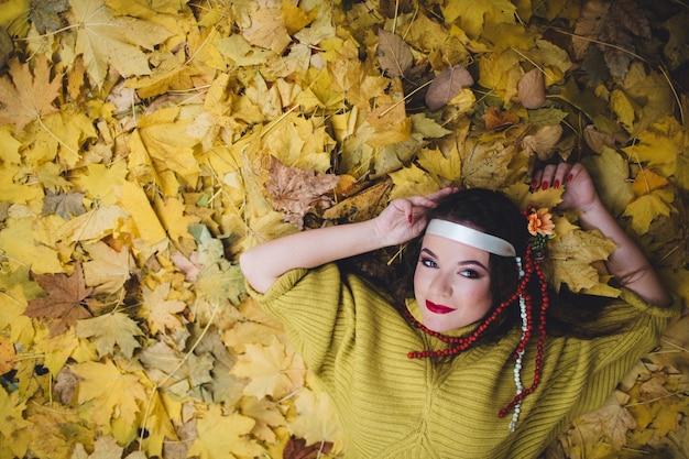 Mulher deitada no chão com folhas secas