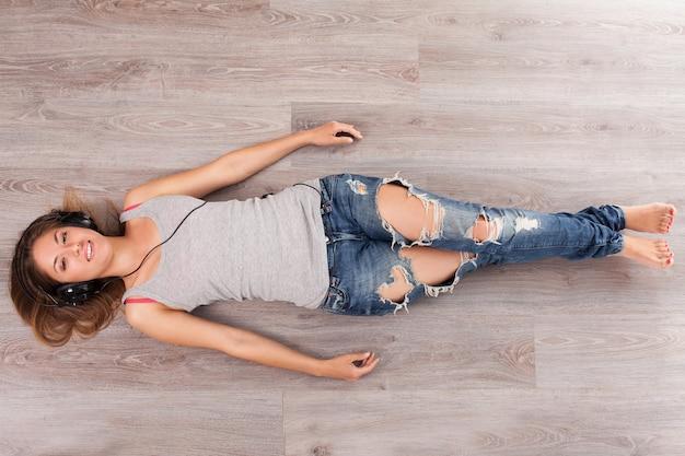 Mulher deitada no chão com fones de ouvido
