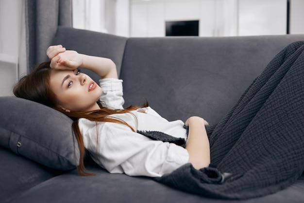 Mulher deitada no sofá coberta com um cobertor segura a mão na cabeça problemas de saúde