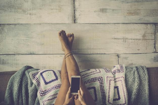 Mulher deitada no sofá com as pernas apoiadas na parede relaxada olhando para o telefone - conceito de menina sozinha em casa com tecnologia - estilo vintage cor cinza