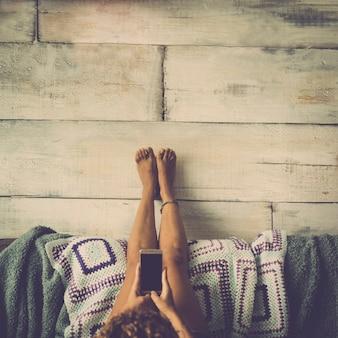 Mulher deitada no sofá com as pernas apoiadas na parede relaxada olhando para o telefone - conceito de menina sozinha em casa com tecnologia - estilo vintage desaturado