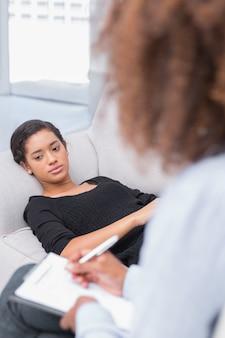 Mulher deitada no sofá dos terapeutas parecendo infeliz