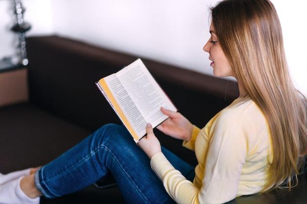 Mulher deitada no sofá e lendo o livro em casa