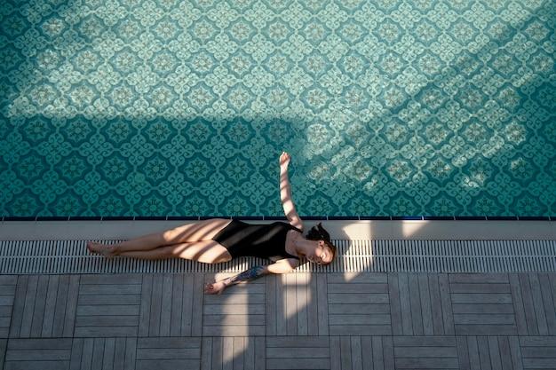 Mulher deitada perto da piscina, tiro completo