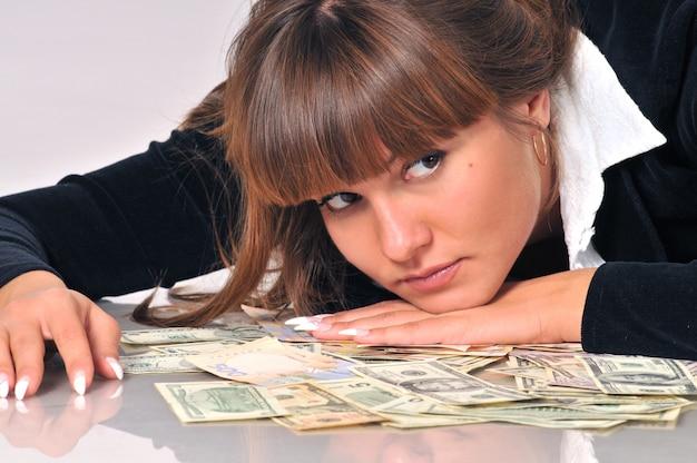 Mulher deitada perto de notas de euro e dólar