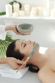 Mulher deitada recebendo um tratamento de beleza facial.