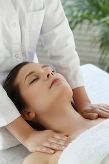 Mulher deitada recebendo uma massagem.