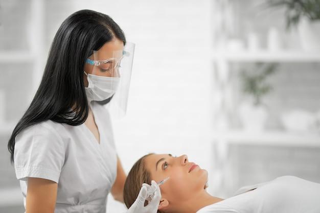 Mulher deitada sobre a pele antienvelhecimento de injeção de procedimento