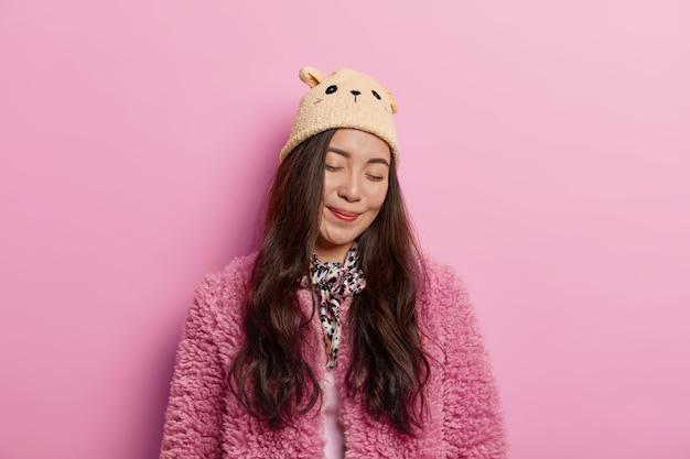 Mulher delicada e delicada fica de olhos fechados e sorriso encantador no rosto, usa chapéu com orelhas e casaco de pele rosado, vira o rosto da câmera