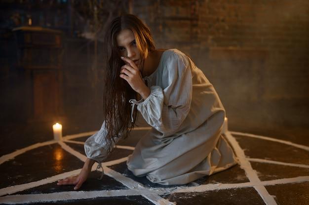 Mulher demoníaca assustadora sentada no círculo mágico, expulsando demônios. exorcismo, ritual paranormal de mistério, religião das trevas, terror noturno