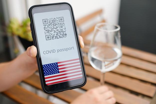 Mulher demonstra pedido de passe covid ou passaporte digital de saúde com código qr e bandeira dos eua em