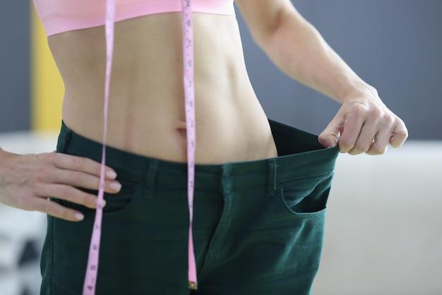 Mulher demonstra resultados de perda de peso na cintura. nutrição adequada e conceito de exercício