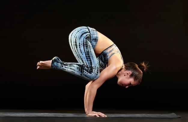 Mulher demonstrando uma pose de corvo no yoga
