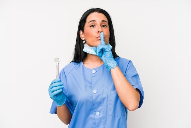 Mulher dentista isolada no fundo branco, mantendo um segredo ou pedindo silêncio.