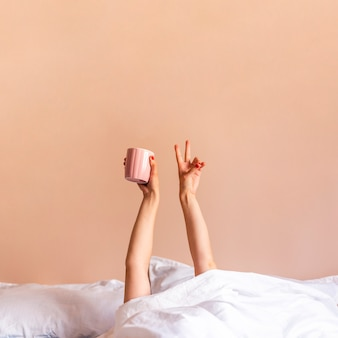 Mulher dentro da cama com as mãos para cima