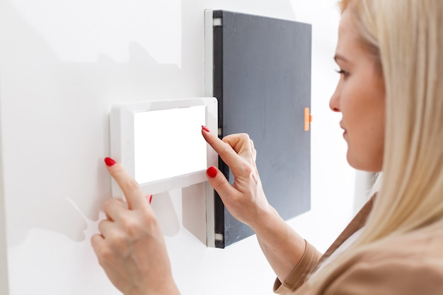 Mulher dentro de casa atendendo telefone de segurança