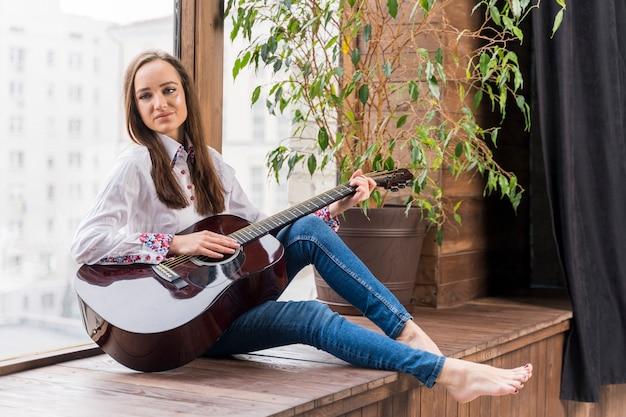 Mulher dentro de casa tocando violão