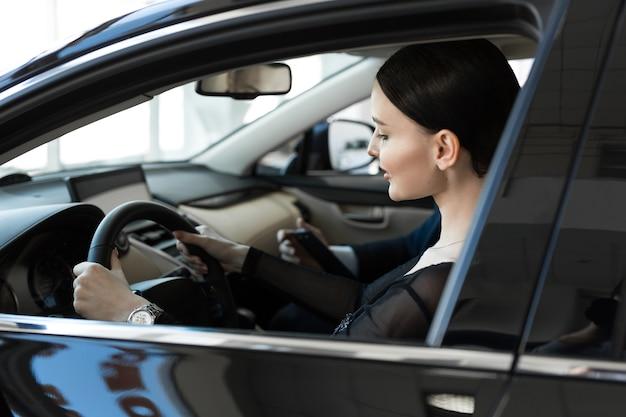 Mulher dentro de um carro em uma concessionária de automóveis