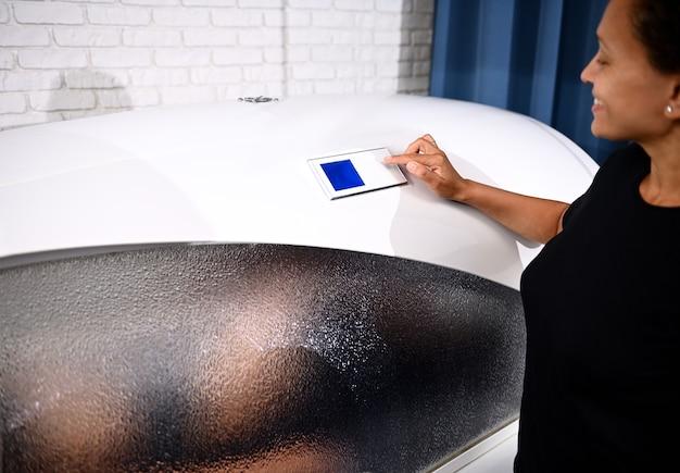 Mulher dentro de uma cápsula de spa. esteticista ajustando programas em cápsula de spa. spa capsule é o sistema perfeito para perda de peso, anti-celulite, anti-envelhecimento, massagem e anti-stress.