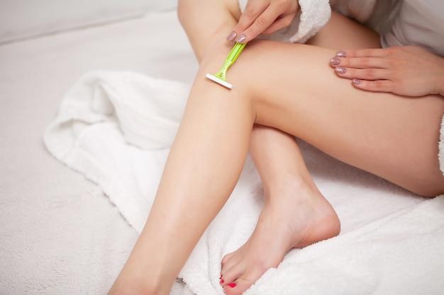 Mulher depila as pernas com uma navalha no banheiro em um apartamento em casa