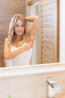 Mulher depilando axila no banheiro