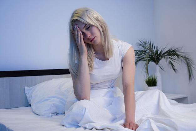 Mulher deprimida acordada durante a noite, ela está exausta e sofrendo de insônia