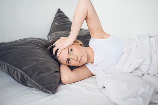 Mulher deprimida, atormentada por um sono inquieto, está exausta e sofre de insônia, pesadelos ou pesadelos, problemas psicológicos. cama ou colchão desconfortável e inconveniente. falta de dormir