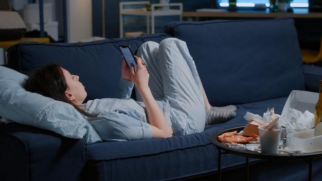 Mulher deprimida chateada ansiosa deitada no sofá, segurando o celular, tentando desbloquear, parecendo mulher perdida com ...