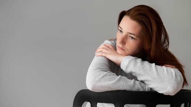 Mulher deprimida com tiro médio, sentada na cadeira