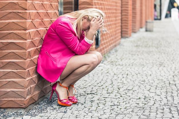 Mulher deprimida contra a parede da cidade